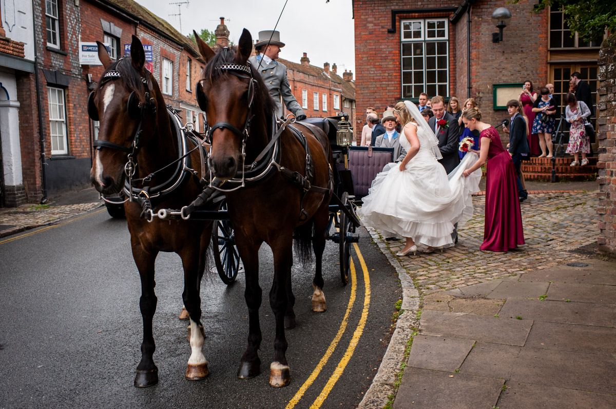 Bride and groom alight horse drawn carriage for wedding