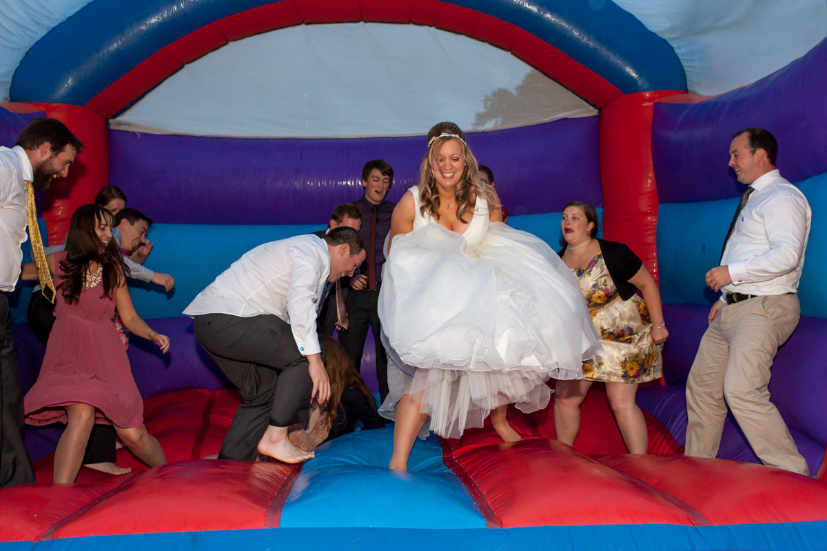 Bride and guests enjoy bouncy castle fun at Latimer Place wedding