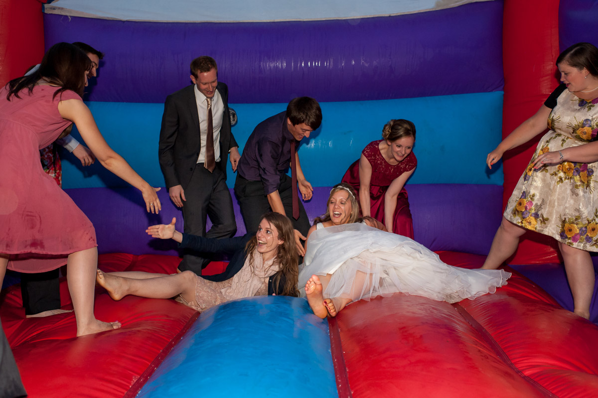 Bride and wedding guest are photographed on bouncy castle at wedding reception
