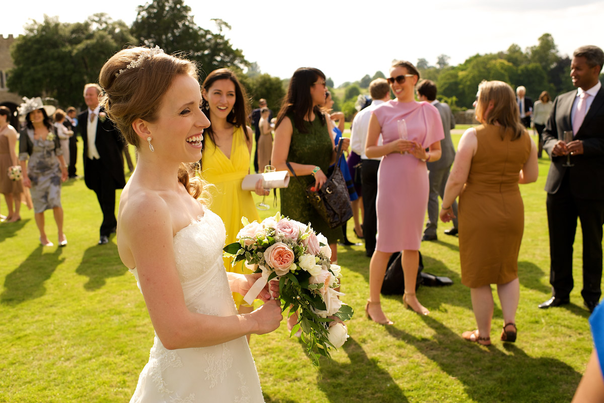 timea laughs with her wedding guests on the lawn at leeds castle in kent
