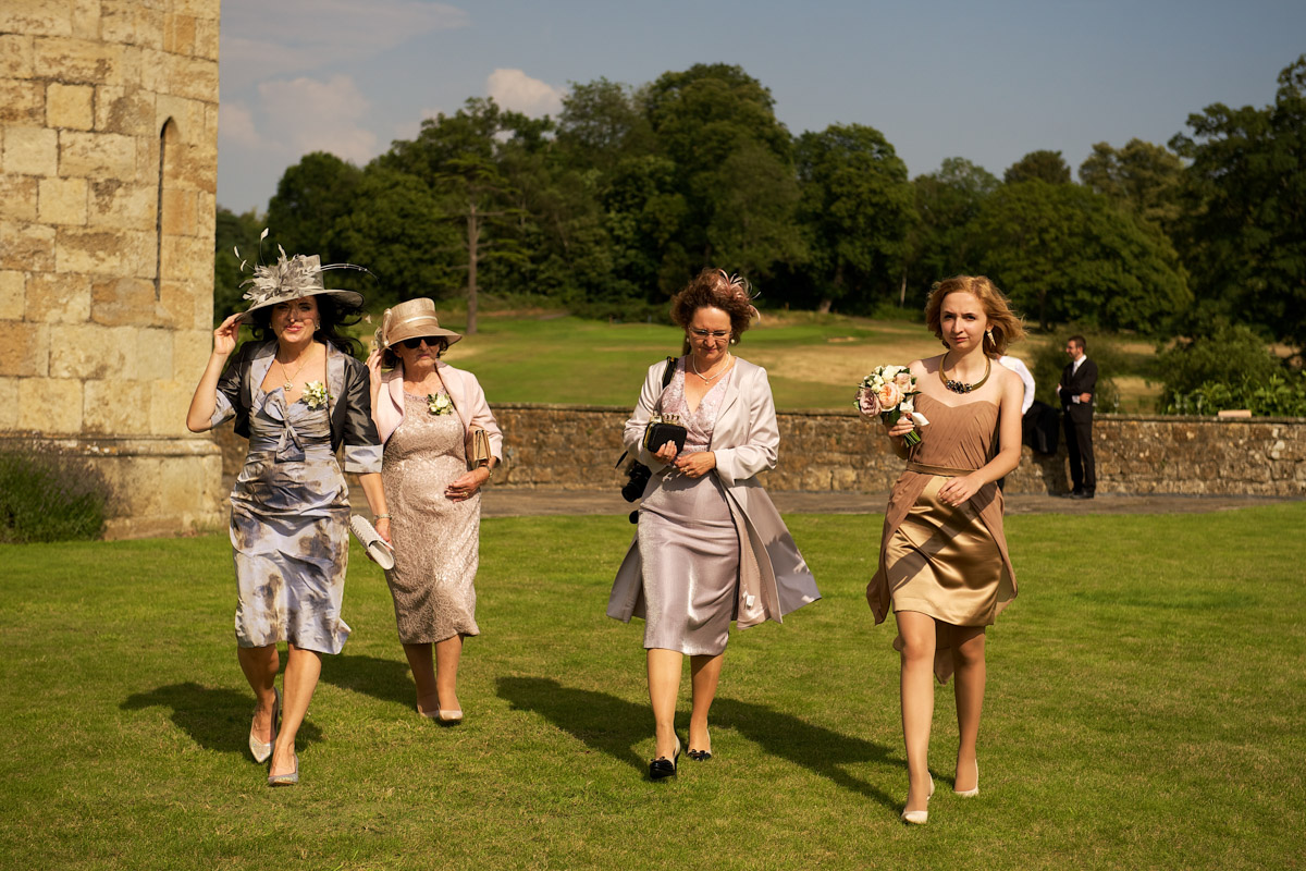 wedding guests walking across lawn outside leeds castle