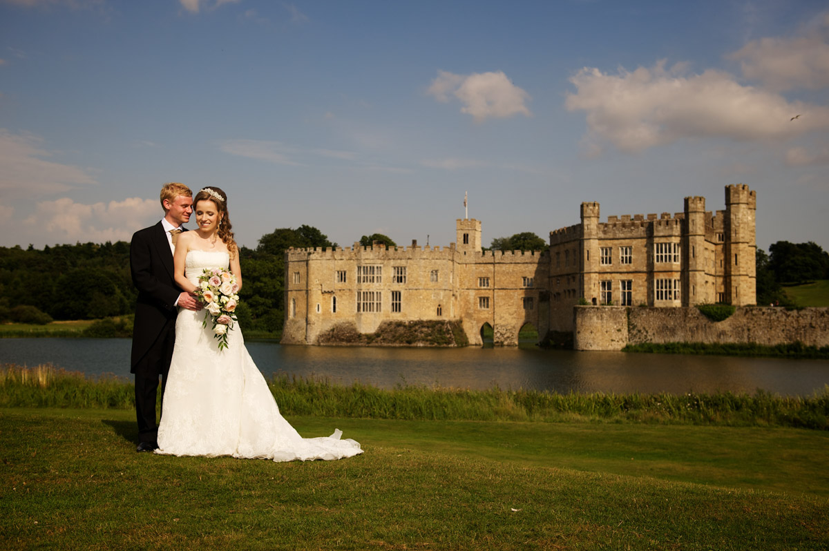 photograph of time and edmund with leeds castle in the background after their wedding there