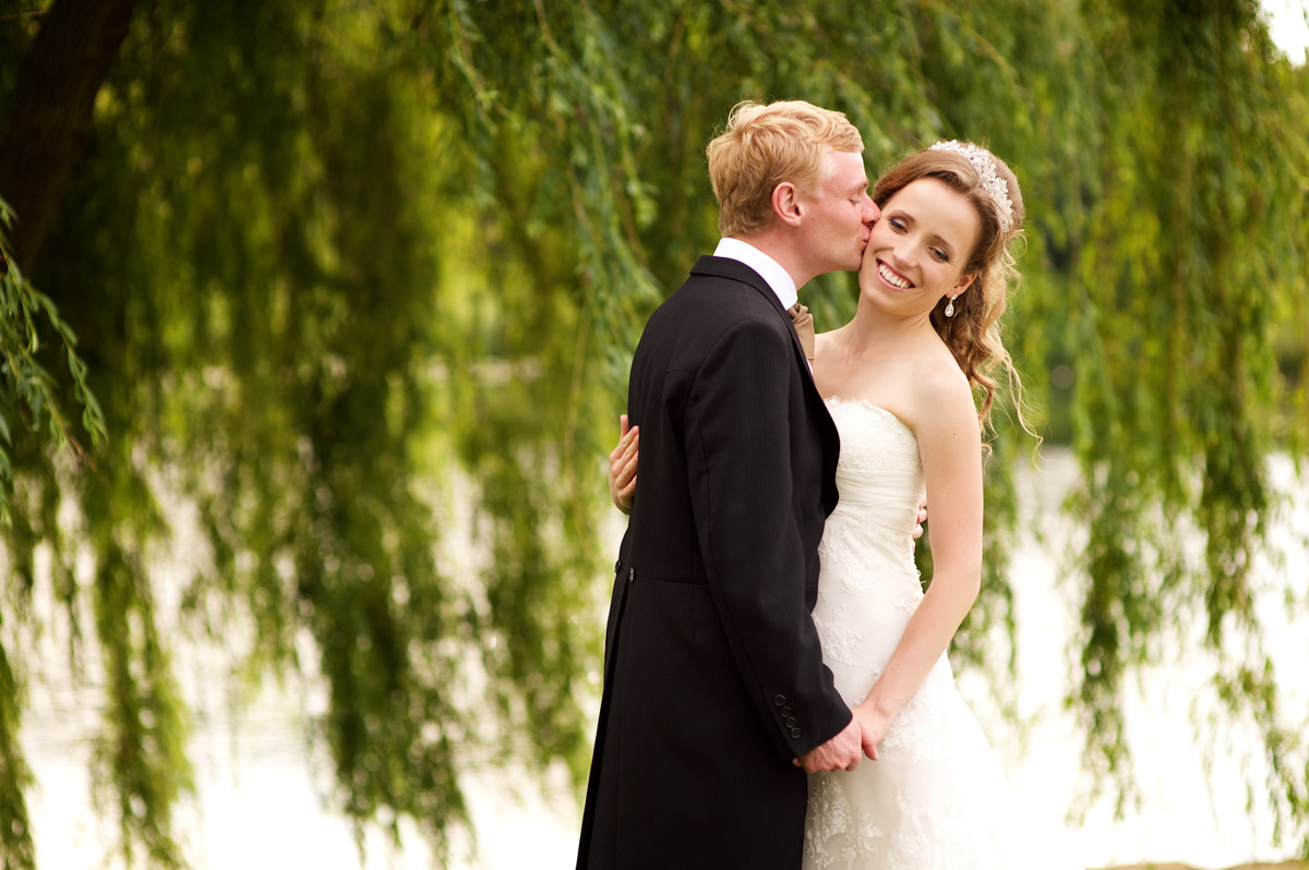 edmund kisses timea on their wedding day at leeds castle with willow tree in background