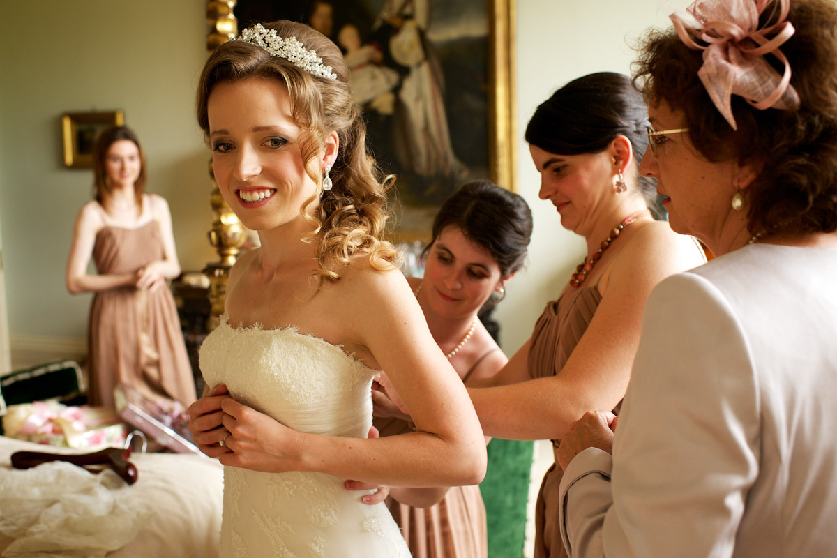 timea has her wedding dress done up by bridesmaids at leeds castle in kent