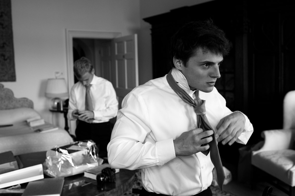 groomsman does up his tie before timea and edmunds wedding at leeds castle