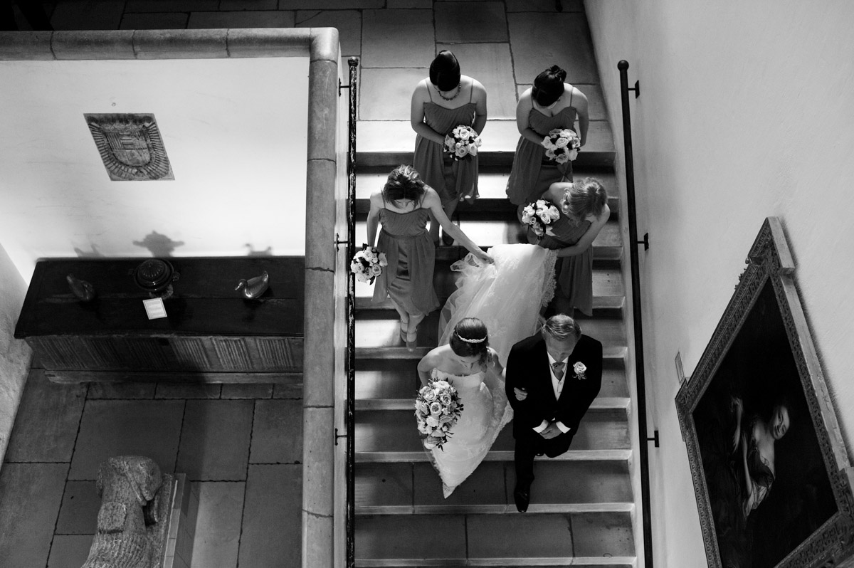bride and bridesmaids walking down the stairs at leeds castle before wedding ceremony