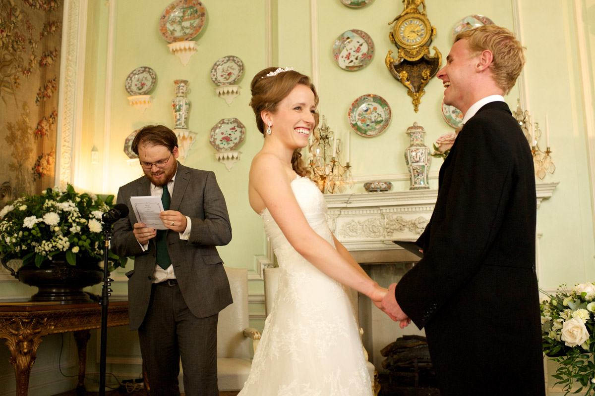 timea and edmund laugh listening to reading during their wedding ceremony at leeds castle in kent