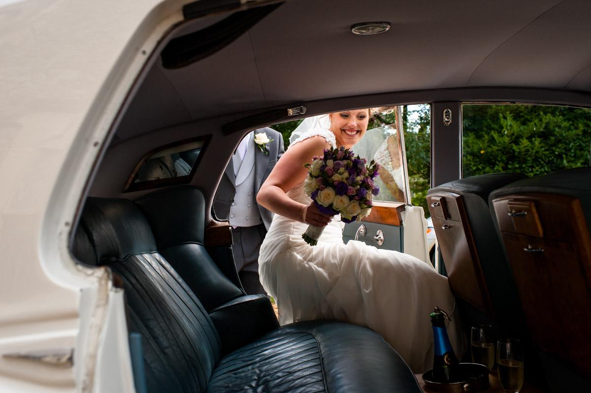 Bride gets into her rolls royce wedding car