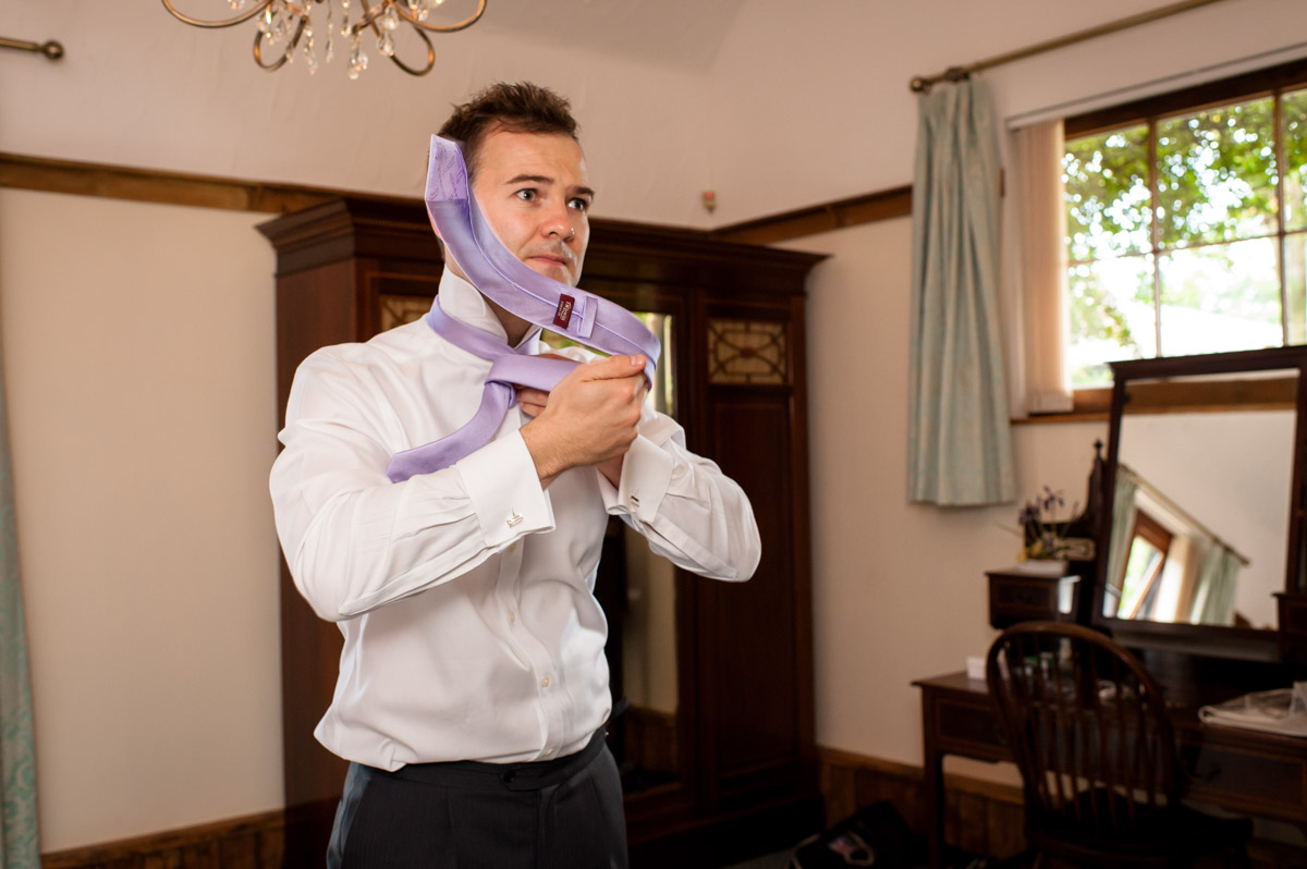 Groom puts his tie on at Winters Barn for his wedding