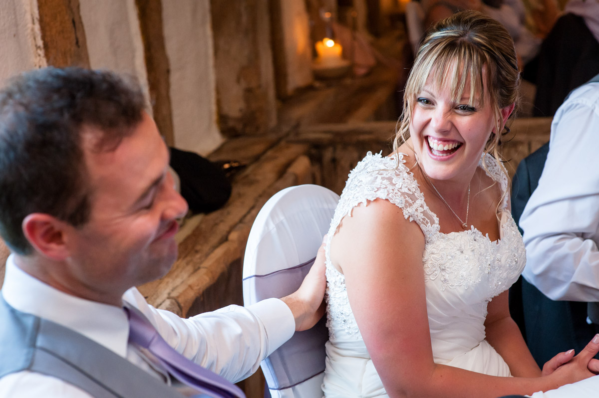 Bride and groom laugh at Best mans speech at Winters Barn
