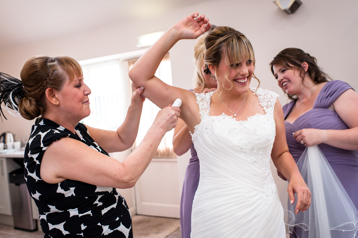 Brides mum and bridesmaids help bride get ready for her wedding Winters Barn