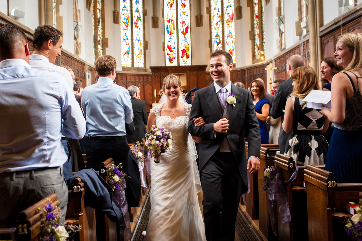 Bride and Groom walk back down the aisle in St Edmunds Chapel after their wedding ceremony