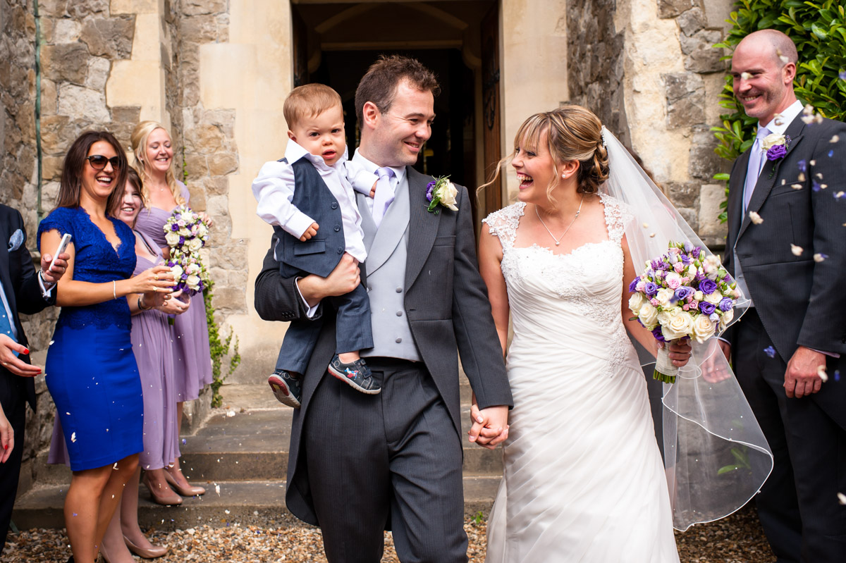 Bride and Groom receive confetti outside St Edmunds Chapel, Canterbury on their wedding day
