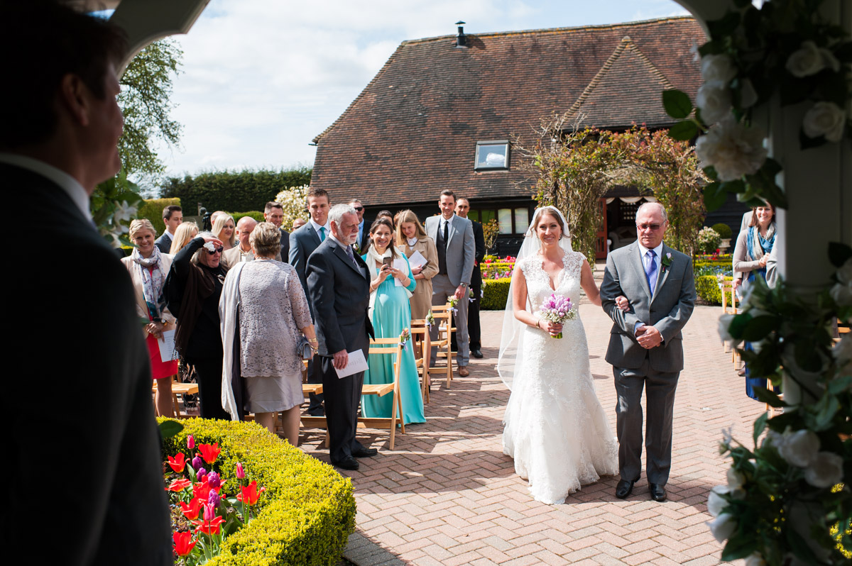 Bronwyn and her father walk up the aisle at the old Kent barn