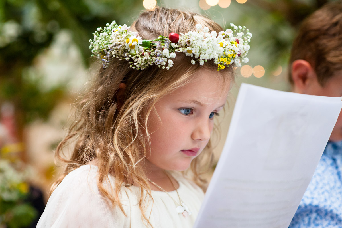 flower girl does wedding reading at rachel and daniels wedding ceremony in glass house at the secret garden in kent