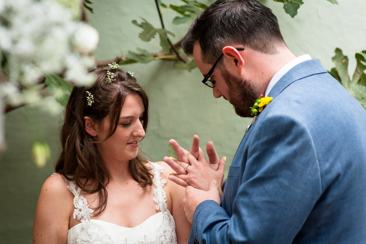 wedding couple look at their wedding rings after ceremony in kent venue, the secret garden