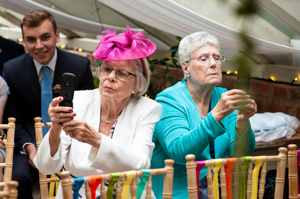 guests at rachel and daniels wedding take photos with their phones