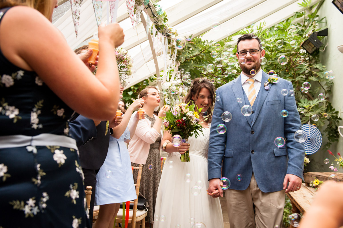 Bubbles, wedding procession, glass house ceremony in the secret garden kent