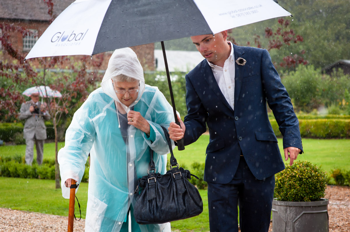 rainy day summer wedding, guests under umbrella