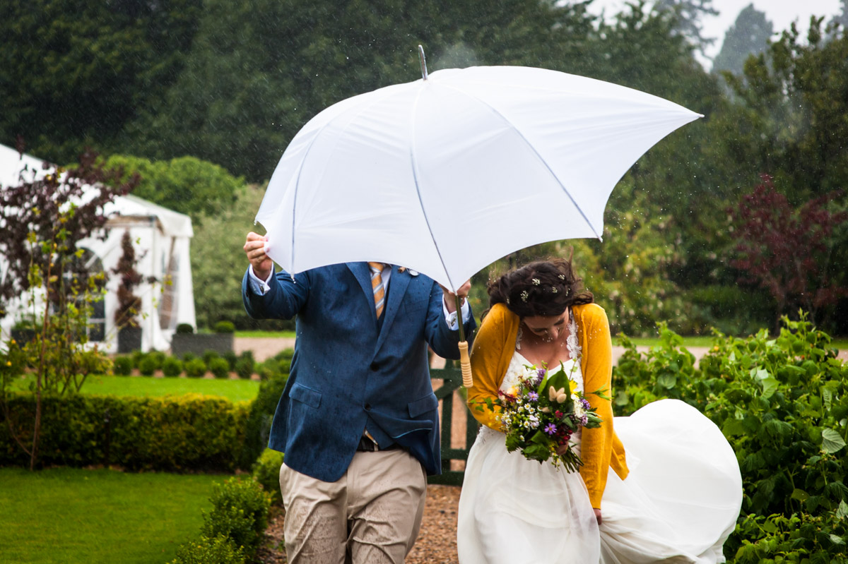 Photograph of rachel and Daniel on their wet wedding at the secret garden in kent