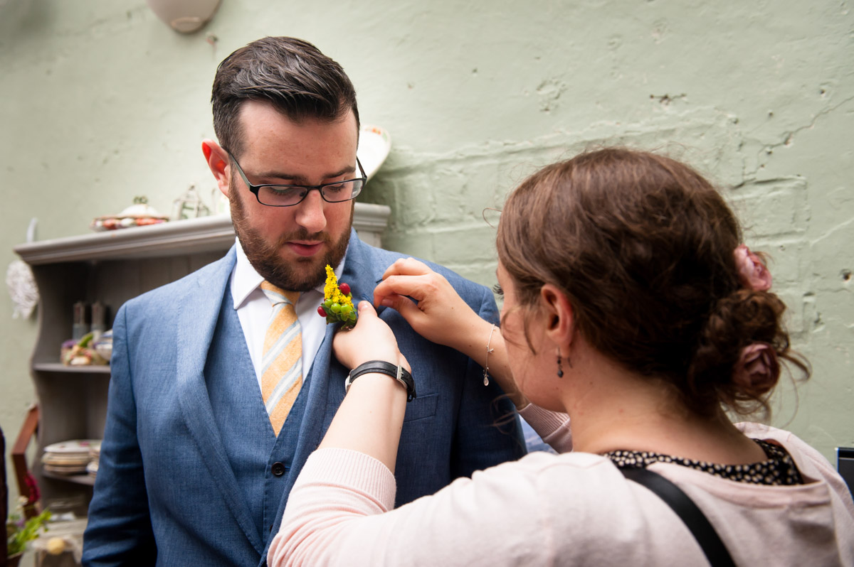 daniel is photographed being helped with button hole at his Secret garden wedding in Kent