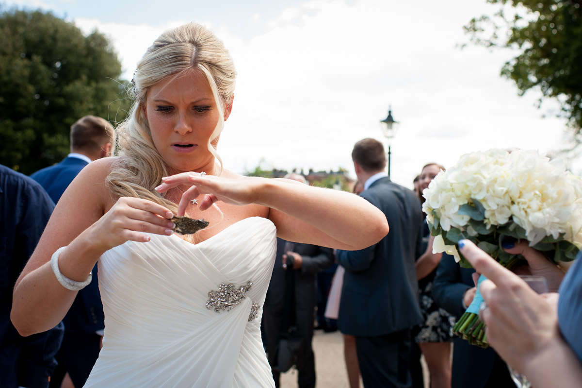 Bride eats oyster at her wedding reception in Whitstable Kent