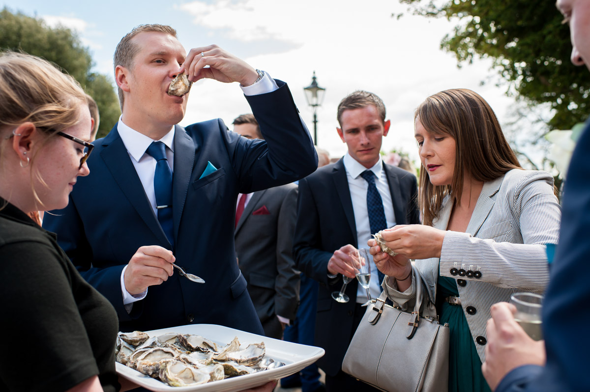 Photograph of groom eating oysters at his wedding reception at Whitstable castle in Kent
