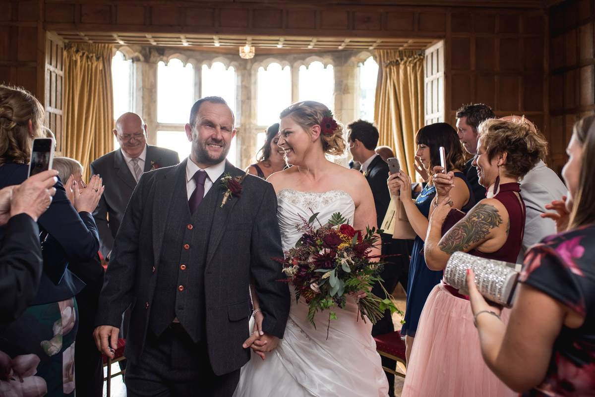 John and Lianne are photographed walking down the aisle after their wedding ceremony at Lympne Castle in kent