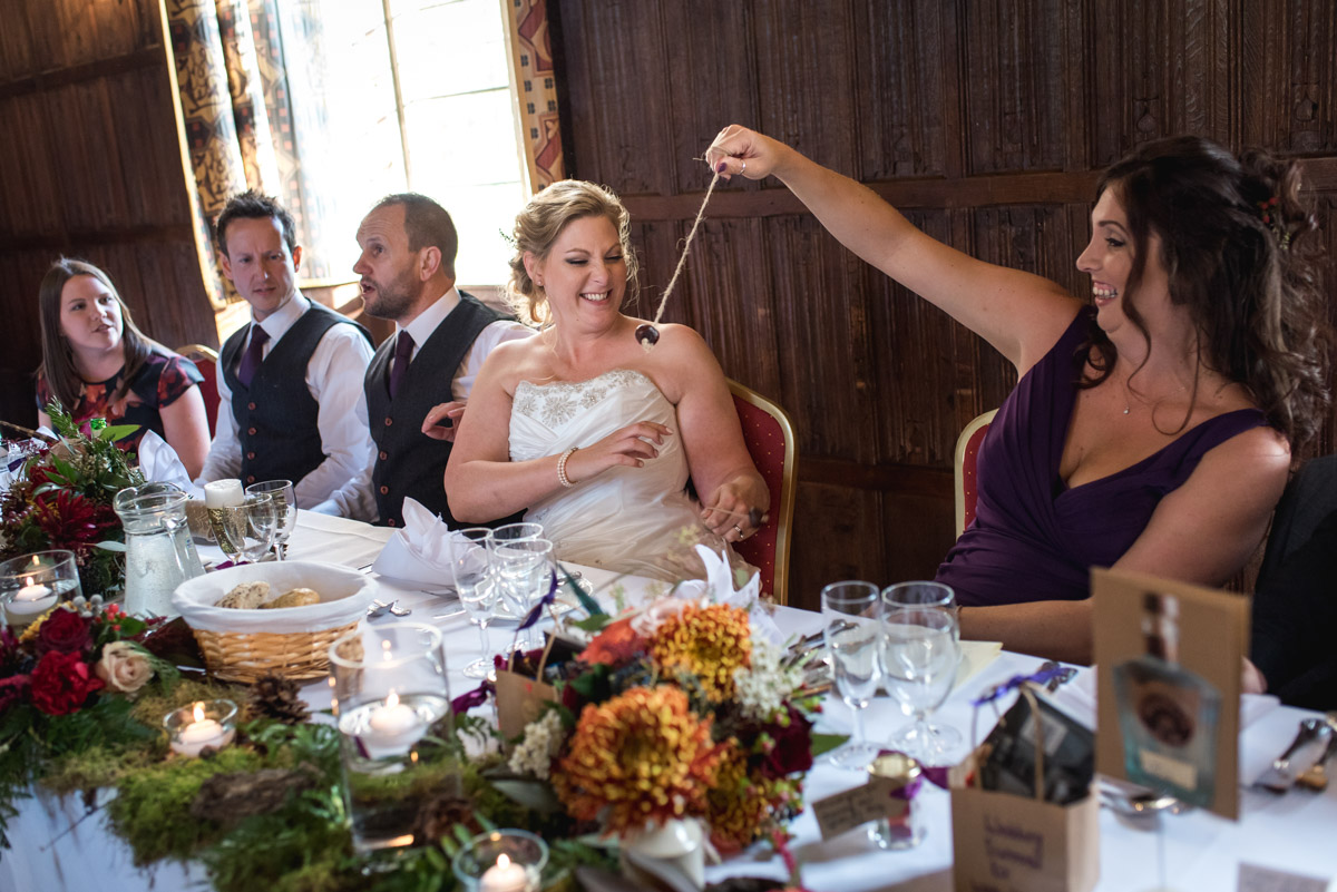 Lianne and her bridesmaid are photographed playing conkers during the reception at Lympne Castle in Kent