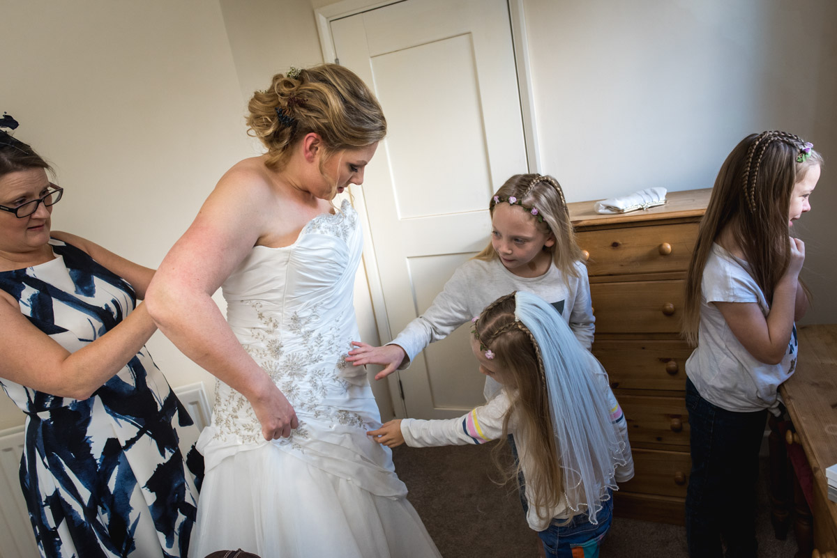 Flower girls inspect Liannes dress while she gets ready for her wedding at Lympne Castle in Kent