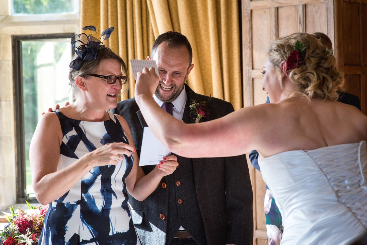 Photograph of Lianne drying her friends tears while she does her wedding reading during the ceremony at Lympne Castle in Kent