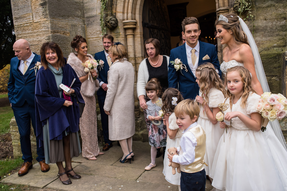 Jade and Stuart photographed with flower girls and page boy outside Kilndown church