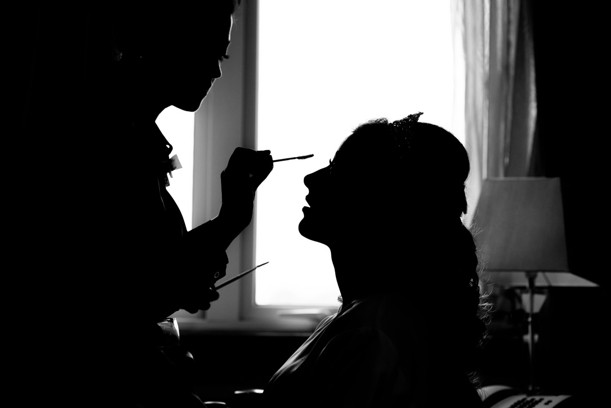 Black and white wedding photograph of Jade having her make up applied