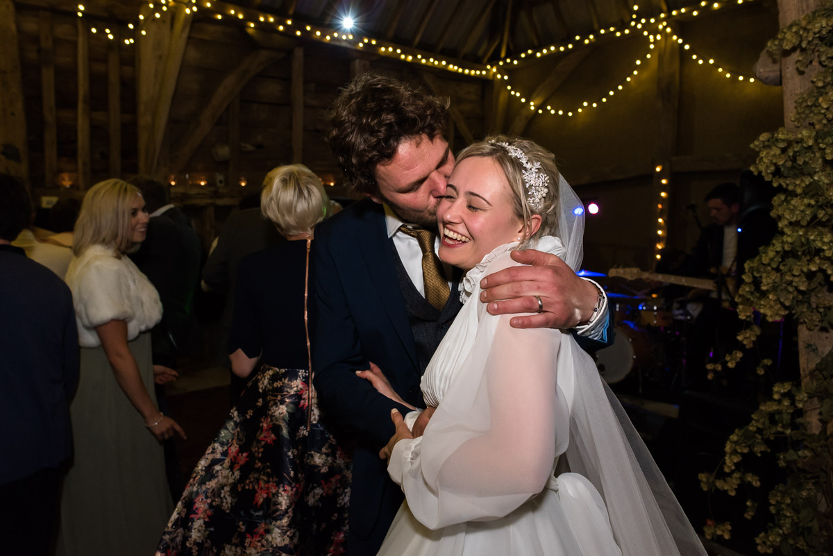 Steven plants a kiss on Janes cheek during their wedding reception after their Chilham church wedding in Kent
