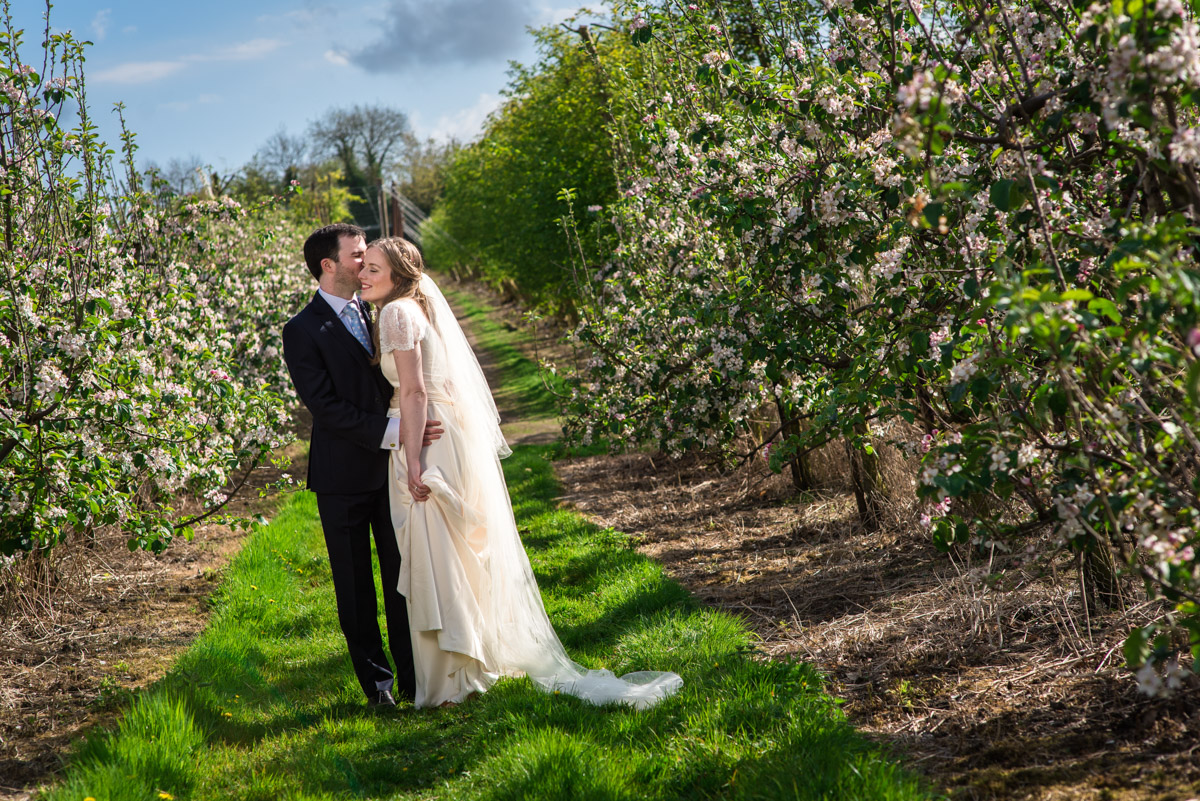 Wedding couple photograph of Flora and James in apple orchards in Brenchley Kent
