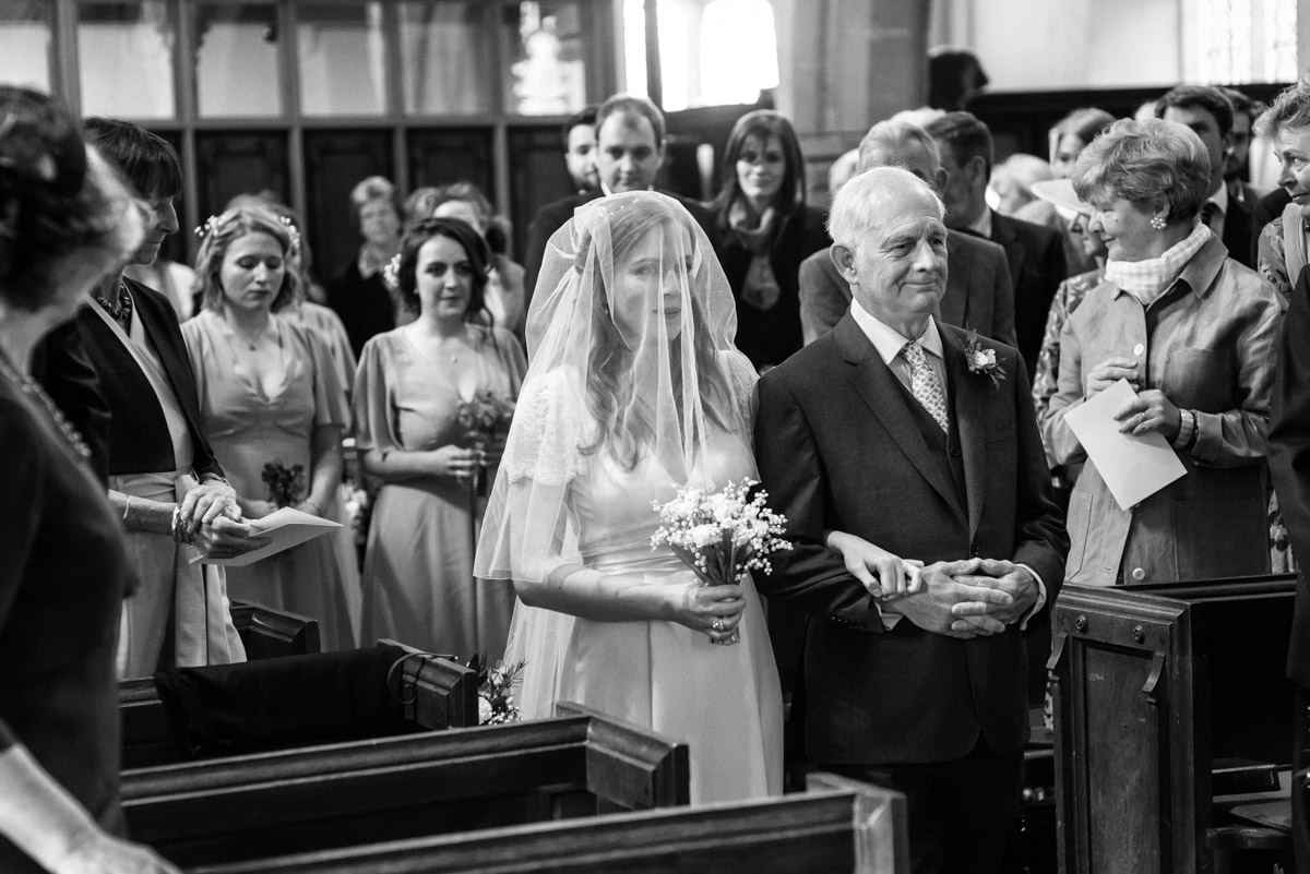 Flora is walked up aisle by father in Brenchley Church in Kent on her wedding day