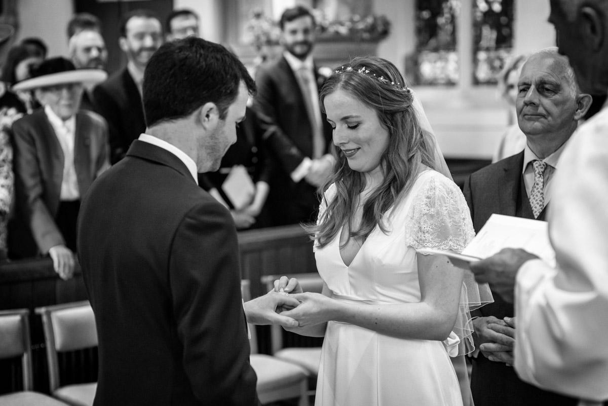 Photograph of Flora putting wedding ring on james during Kent wedding