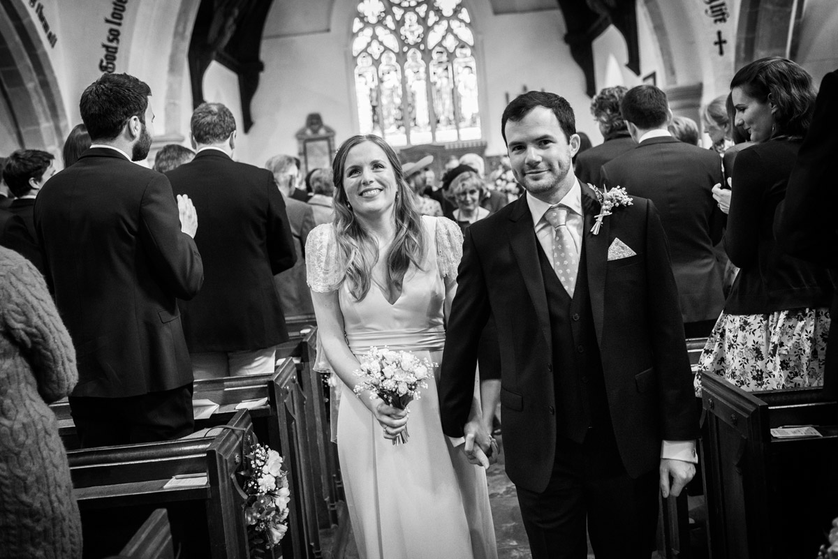 Flora and James photographed leaving church after their wedding ceremony