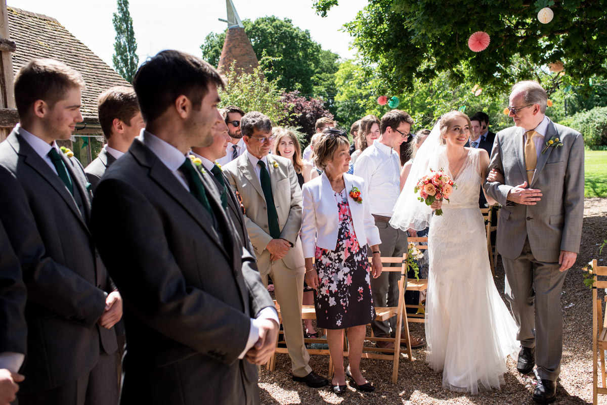 Bride is walked up the aisle by father for her wedding ceremony at Ratsbury Barn in Kent