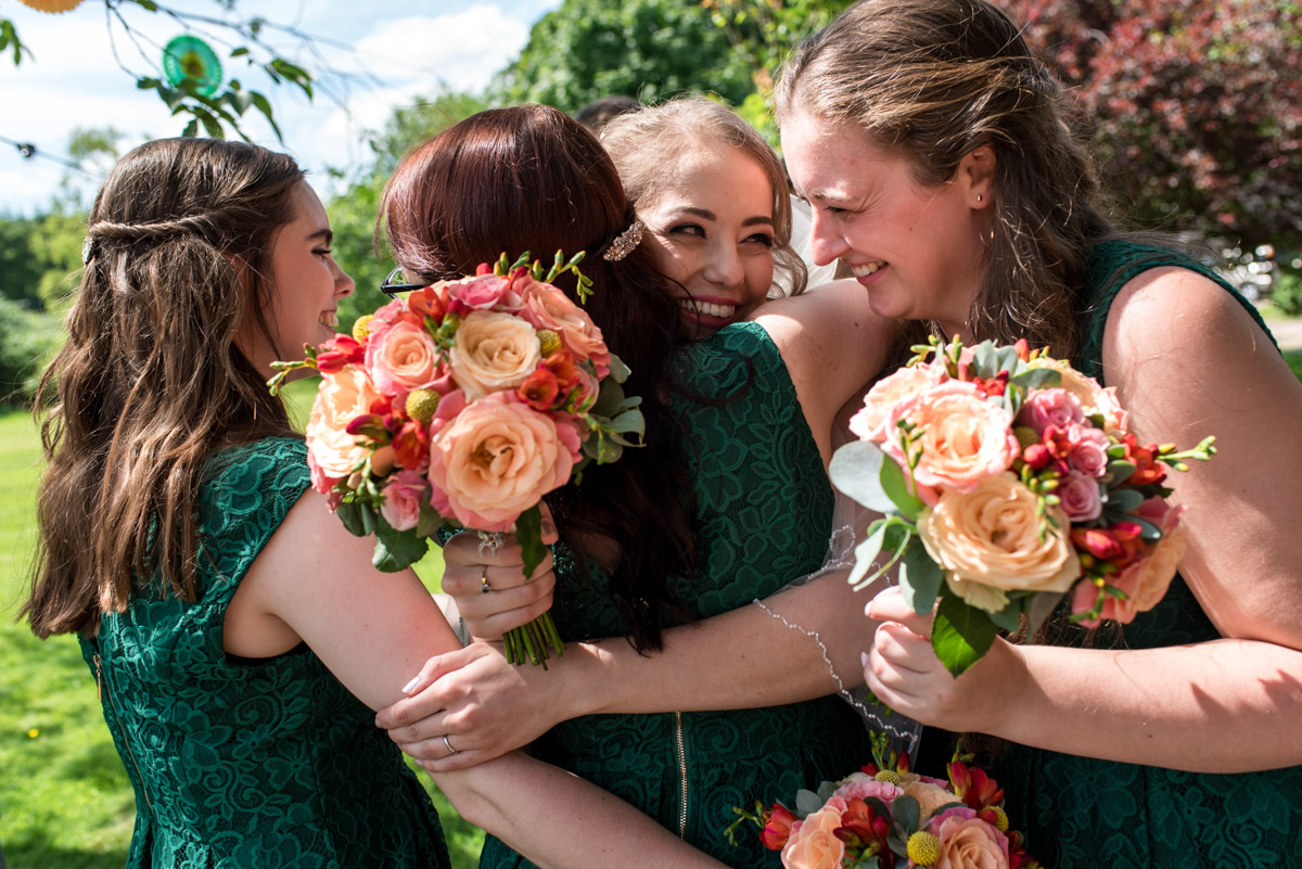 Beth hugs her bridesmaids after her wedding at Ratsbury Barn in Kent