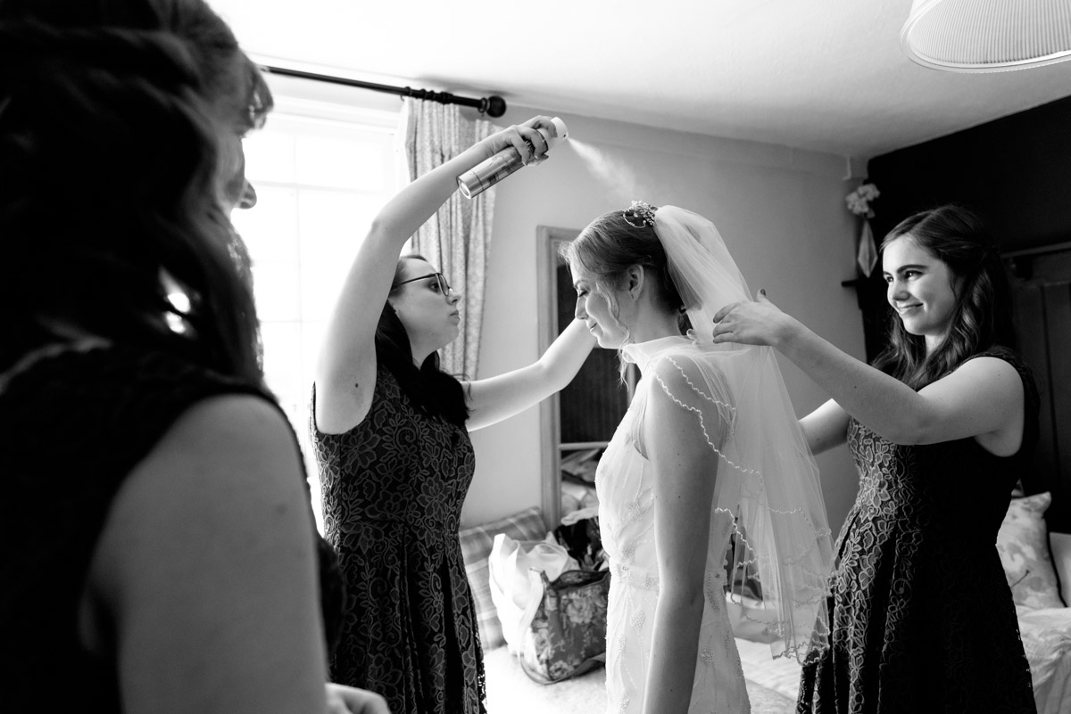 Bridesmaids are photographed applying hairspray before Beth and Toms Ratsbury Barn wedding in Kent