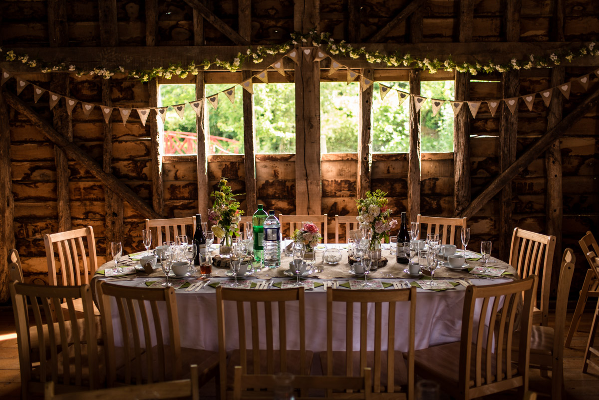 Photograph of top table inside Ratsbury Barn in Kent on Tom and Beths wedding day