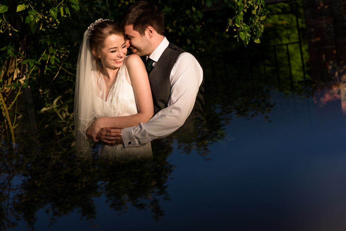 Beth and Tom are photographed embracing during quiet moment together after their wedding at Ratsbury Barn