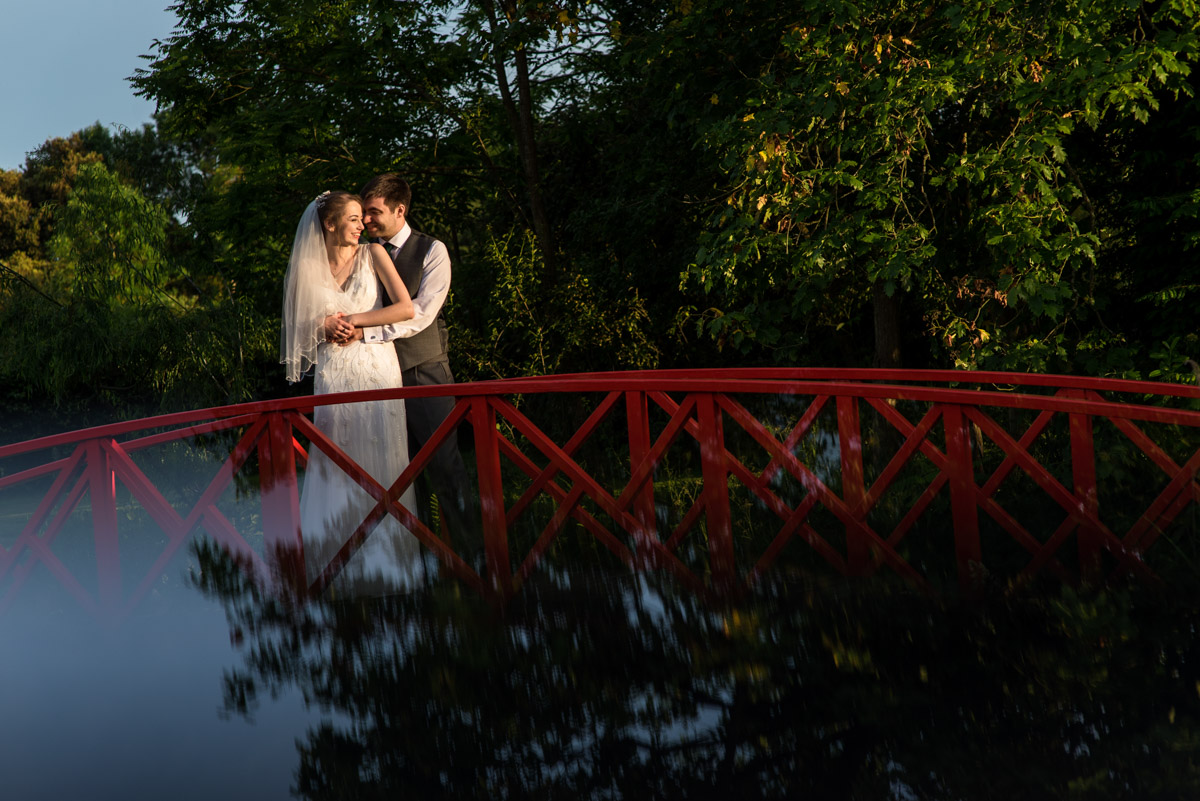 Beth and Tom on red foot bridge, Ratsbury Barn photography in Kent