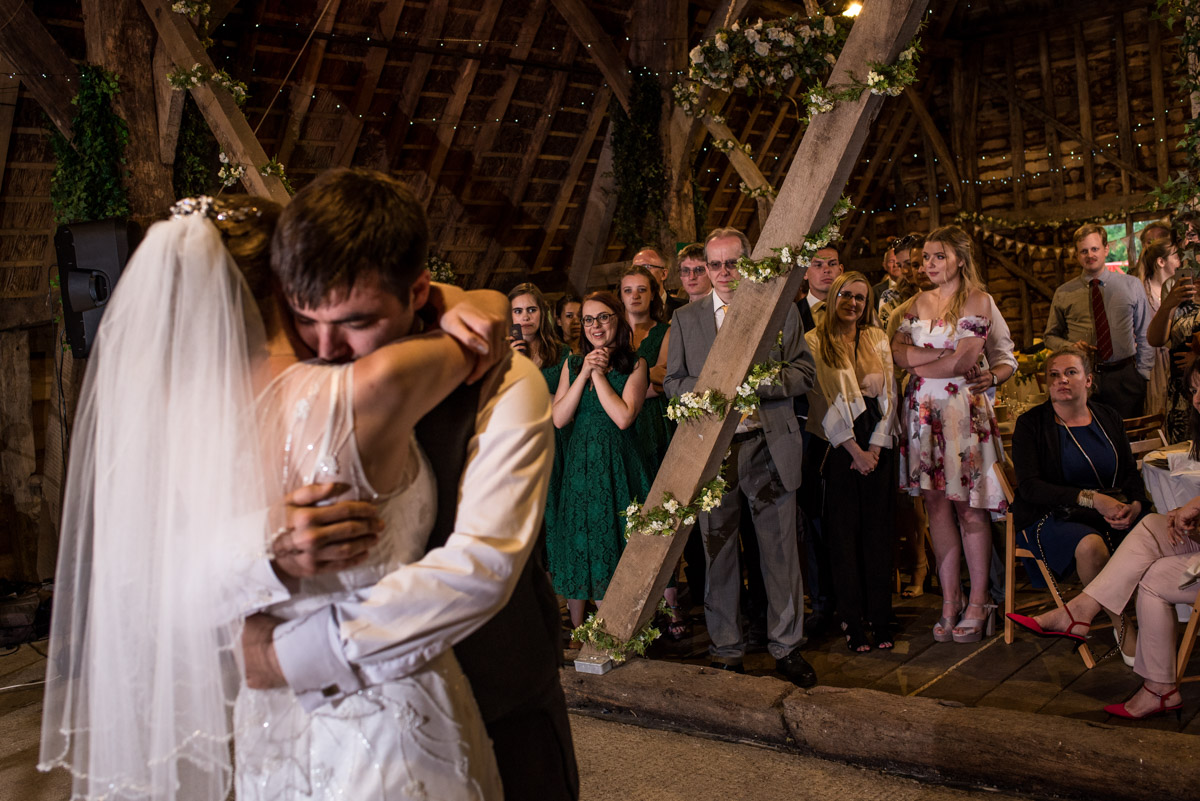 Beth and Tom embrace during their first dance on their wedding day at rats bury Barn