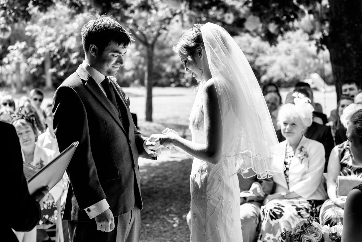 Beth places Toms wedding ring on his finger during their ceremony at Ratsbury barn in Kent
