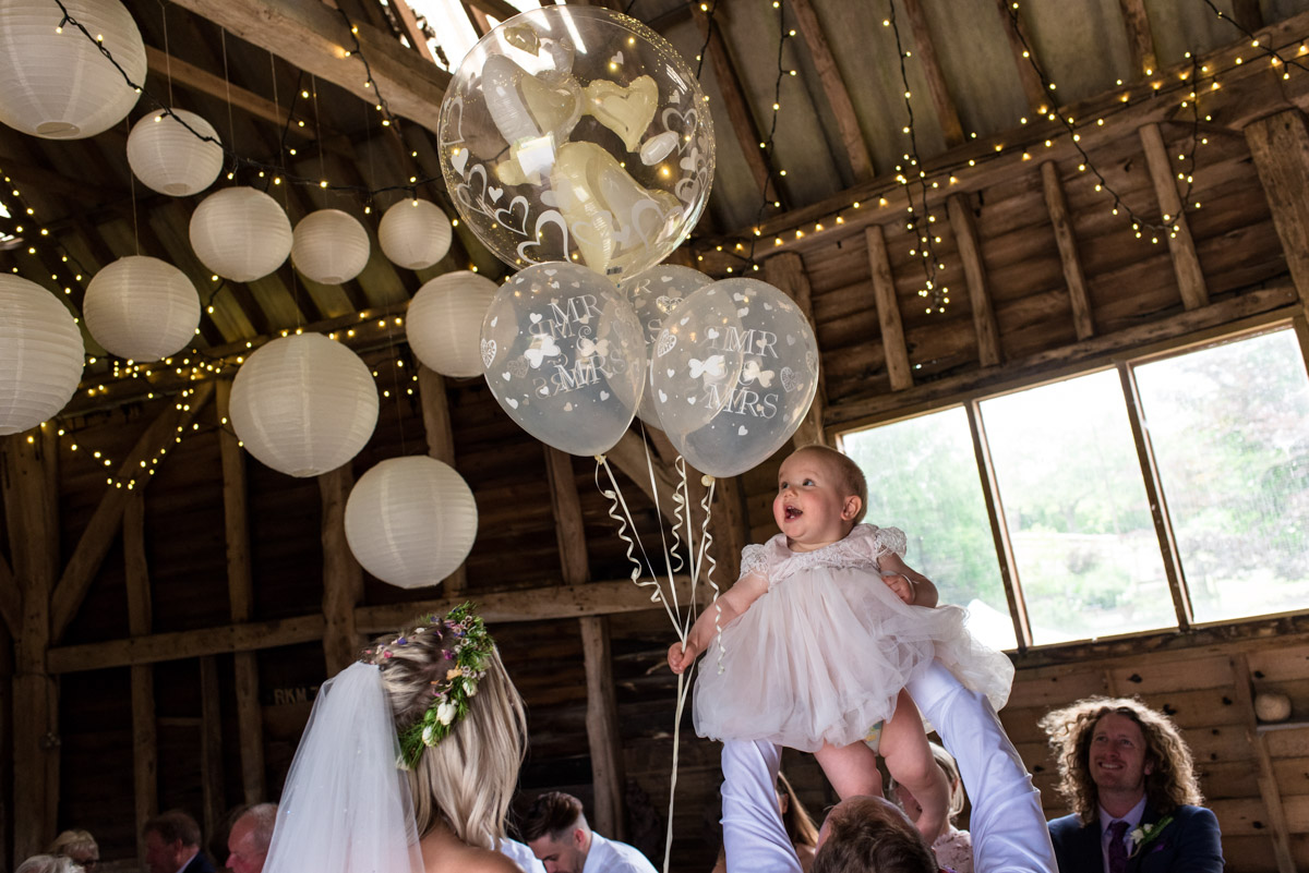 Photograph of baby and balloons at Anne and Joshs Kent summer wedding