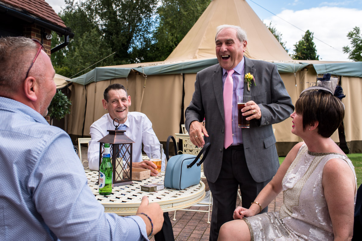 Debbie father laughing with other wedding guests