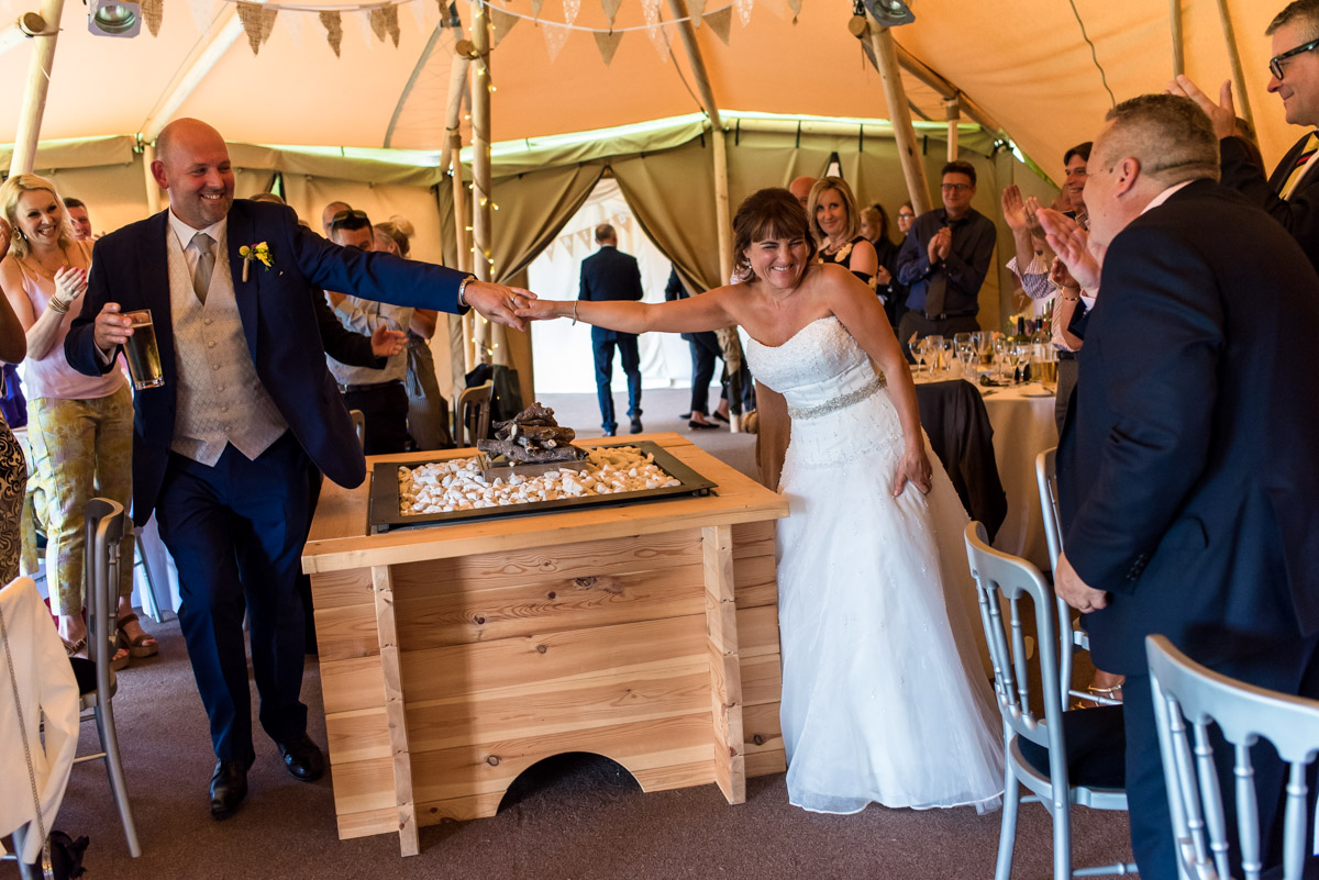 Photograph of Martin and Debbie entering the tipis for their wedding reception