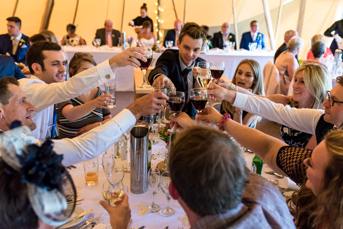 Tipi wedding photography in kent. Guests toast the bride and groom